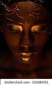 Close up portrait of beautiful african woman with creative gold make-up and turban