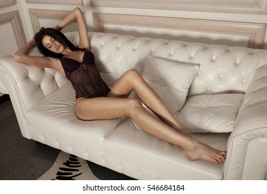 close up portrait of beautiful alluring young woman in purple sexy lingerie lying in sofa