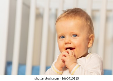 Close portrait of beautiful baby boy at toddler age with hands near face sitting in front of crib