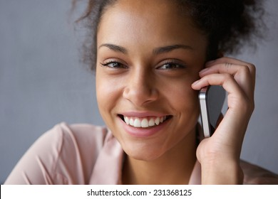Close up portrait of a beautiful black woman smiling with mobile phone