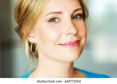 Close up portrait of beautiful blond woman with blue eyes, wearing professional makeup