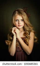 Close up Portrait of a Beautiful blonde girl with blue eyes in a brown vintage dress and bow .Pretty child with shiny curly hair posing in studio on dark background.