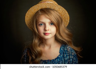 Close up Portrait of a Beautiful blonde girl with blue eyes in vintage dress and hat .Pretty child with shiny curly hair posing in studio on dark background.