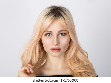 Close up portrait of a beautiful blonde girl with nice face, full lips and blue eyes.