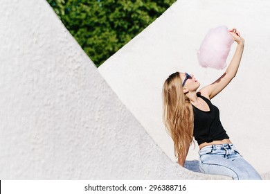 Close up portrait of beautiful blonde girl sitting outside with pink cotton candy. Wearing sunglasses with stars. Red lips. White background, not isolated.
