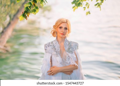 Close Up portrait. beautiful blonde woman in a white creative royal cloak with feathers. Decorated and embroidered with silver sparkling stones. Background nature, water tree. glamorous art queen