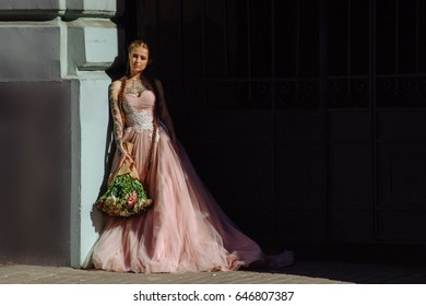 Close up portrait of beautiful bride with tattoo and long hair in braids. Girl dressed in a classic wedding pink dress. Fashion concept in the street.