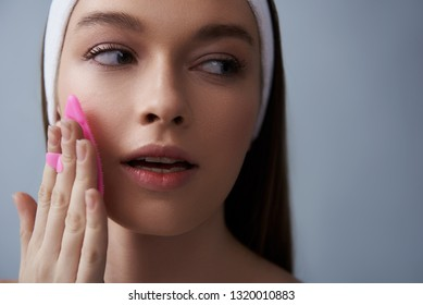 Close up portrait of beautiful brunette girl in white headband massaging cheek with pink massage scrubber. She looking away and keeping mouth slightly open