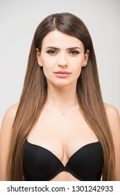 Close up portrait of beautiful brunette women with a slim figure in black bra. Model snaps in the studio on white background