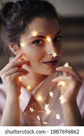 Close up portrait of a beautiful brunette young girl with beautiful big eyes posing with starlights on her skin. Celebration concept