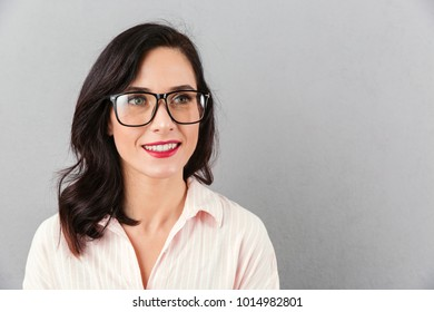 Close up portrait of a beautiful businesswoman in eyeglasses looking away at copy space isolated over gray background