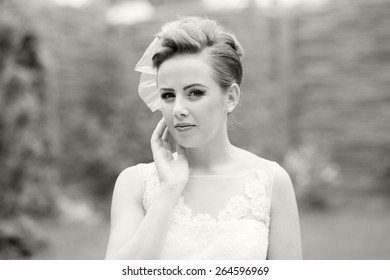 Close up portrait of a beautiful, caucasian, long haired woman wearing a wedding dress, looking happy and melancholic. Black and white photography