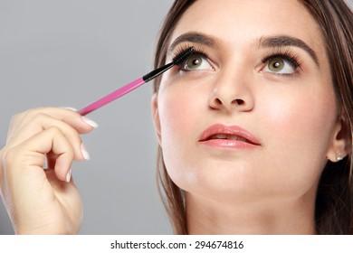 close up portrait of beautiful caucasian model applying mascara