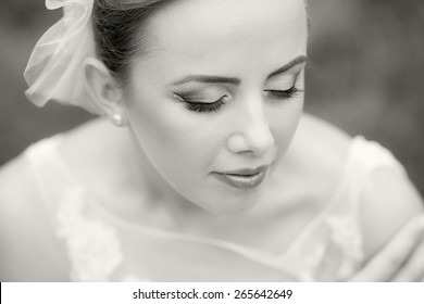 Close up portrait of a beautiful, caucasian woman wearing a wedding dress with natural background. Black and white photography