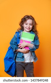 close up portrait of beautiful clever curly girl with copybook notebook wearing jeans jacket blue bright backpack isolated yellow background