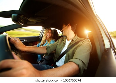 Close up portrait of beautiful couple laughing in car on road trip