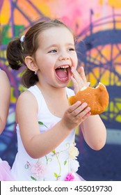 Close up portrait to beautiful cute little toddler girl funny eating