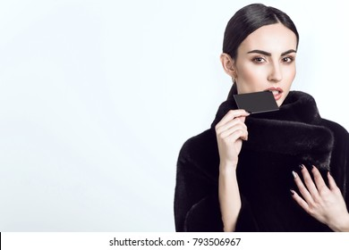 Close up portrait of beautiful dark-haired model with sleek low ponytail wearing dark mink fur coat and biting the edge of a black blank visit card. Isolated on white background. Copy space. Mock up