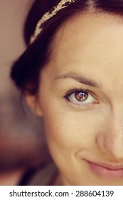 Close up portrait of a beautiful dark-haired smiling woman with headband