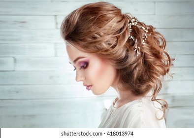 Close up Portrait of a beautiful fashion bride in studio.Perfect make up and hairstyle.Wedding accessories on shiny blonde hair. Pretty sensual young woman dreaming and looking down