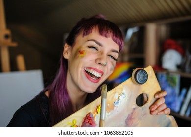 Close up portrait of beautiful female artist with purple hair and dirty hands with different paints on them, holding paintbrushes and laugh in her art studio.
