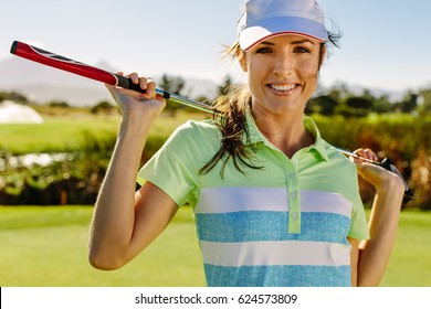 Close up portrait of beautiful female golfer holding golf club on field. Young woman standing on golf course and smiling.