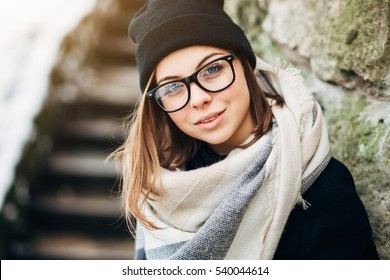 Close up portrait of a beautiful girl with blue eyes in black glasses in a hat and coat with scarf in the winter park