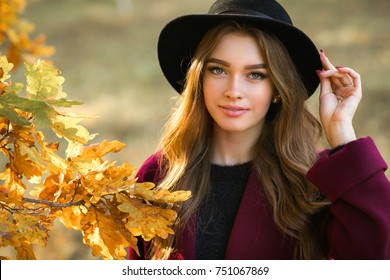 Close up portrait of a Beautiful girl in a claret coat and black hat standing near colorful autumn leaves. Art work of romantic woman .Pretty tenderness model looking at camera.