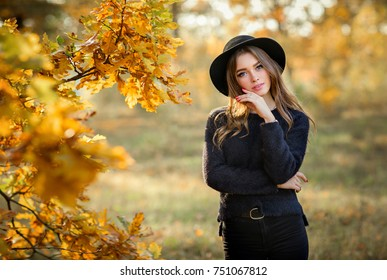 Close up portrait of a Beautiful girl in dark dress and black hat standing near colorful autumn leaves. Art work of romantic woman .Pretty tenderness model looking at camera.