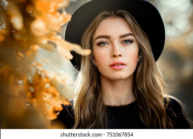 Close up portrait of a Beautiful girl in a dark dress and black hat standing near colorful autumn leaves. Art work of romantic woman .Pretty tenderness model looking at camera.