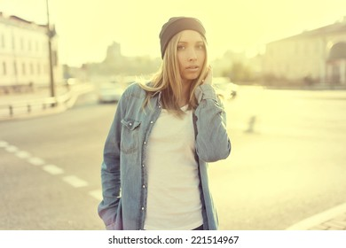 Close portrait of a beautiful girl in a hat against the sun in