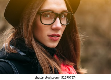 Close up portrait of beautiful girl in hat and glasses sitting on bench in sunny autumn park