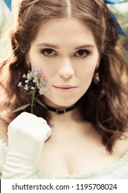 close up portrait of beautiful girl in historical dress, gloves, with a flower in her hands in the park