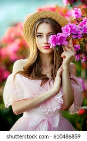 Close up portrait of a Beautiful girl in a pink vintage dress and straw hat standing near colorful flowers and hiding. Art work of romantic woman .Pretty tenderness model  looking at camera
