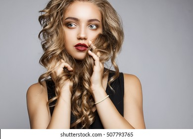 Close portrait of a beautiful girl with a professional make-up and hairstyle. Attractive face of a young girl on a gray background. Girl holding hands near face and holds the hair