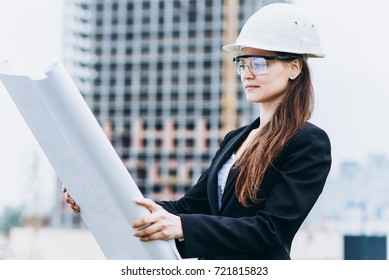 Close up portrait of beautiful girl in a yellow protective helmet and protective glasses, an architectural concept