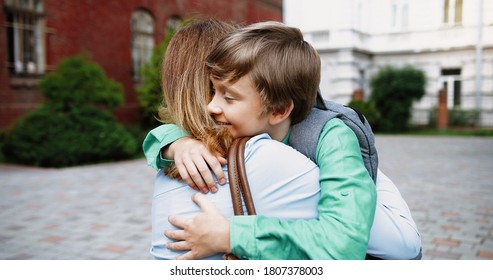 Close up portrait of beautiful happy Caucasian woman hugging her son at schoolyard outdoors. Cheerful teen male junior student with school bag hugs mother near school. Love concept