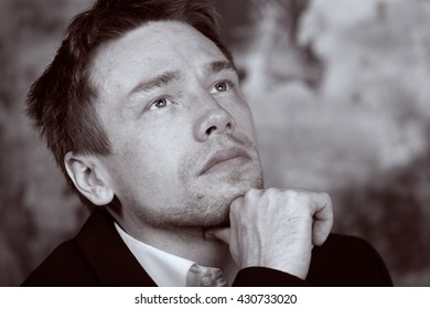 Close portrait of a beautiful imposing man. Blond. Dressed in a classic formal suit. Pensive. Looks into the distance. Vintage Black and White colour graded.