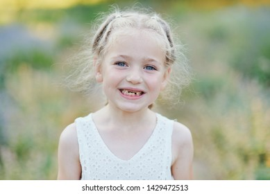 Close up portrait of beautiful joyful blonde Caucasian girl smiling demonstrating white teeth without two front teeth. Cheerful child.