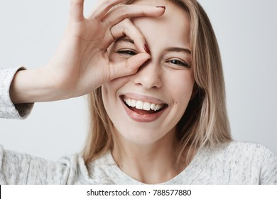 Close up portrait of beautiful joyful blonde Caucasian female smiling, demonstrating white teeth, looking at the camera through fingers in okay gesture. Face expressions, emotions, and body language - Shutterstock ID 788577880