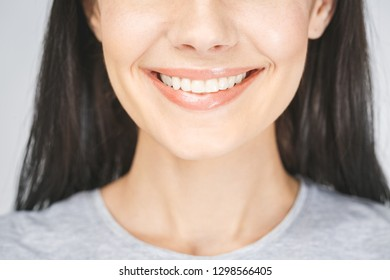 Close up portrait of beautiful joyful female smiling, demonstrating white teeth, looking at the camera. Face expressions, emotions, and body language.