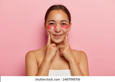 Close up portrait of beautiful korean female wears cosmetic patches under eyes for puffiness, keeps index fingers on cheeks, smiles gently, poses shirtless, avoids dark circles and wrinkles on face