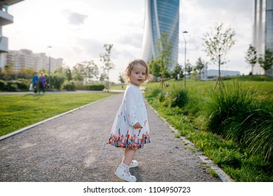 Close up portrait of beautiful little girl with curly blonde hair in beautiful white dress standing on the pathway. Skycrapers background. Urban city. Sunny day