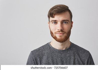 Close up portrait of beautiful manly bearded guy with stylish hairstyle smiling, looking in camera with happy and calm face expression.