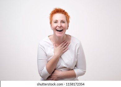 Close up portrait of a beautiful mid adult woman with red hair laughing standing on gray background. She is impressed and out of mind