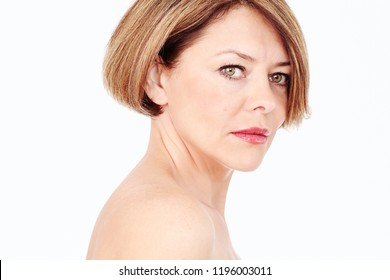 Close up portrait of beautiful middle aged woman with short brown hair, fresh makeup, naked shoulders and neck over white background - mature beauty, skin care or anti age concept