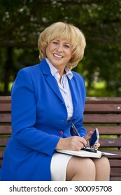 Close up portrait of a beautiful middle aged woman in a blue business suit