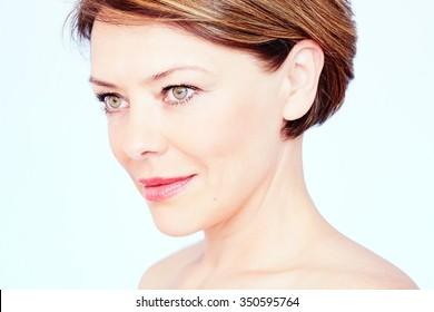 Nahaufnahme eines Porträts von schöner Frau mittleren Alters mit kurzen braunen Haaren, roten Lippen und frischem Make-up auf blauem Hintergrund - Schönheitskonzept