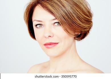 Nahaufnahme eines Porträts einer schönen Frau mittleren Alters mit kurzen braunen Haaren, roten Lippen und frischem Make-up auf weißem Hintergrund - Schönheitskonzept