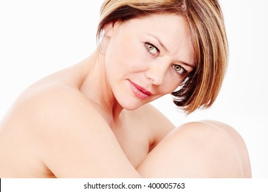 Close up portrait of beautiful middle aged woman with short brown hair, red lips and fresh makeup hugging her knees over white background - beauty, skin care or anti aging concept